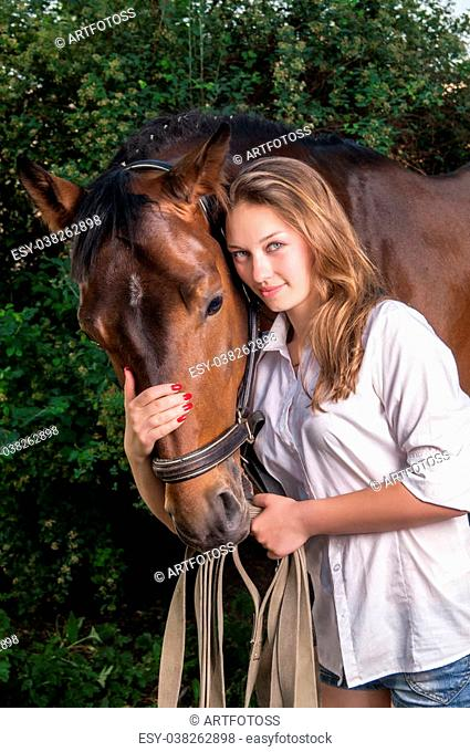 Beautiful young woman near the chestnut horse