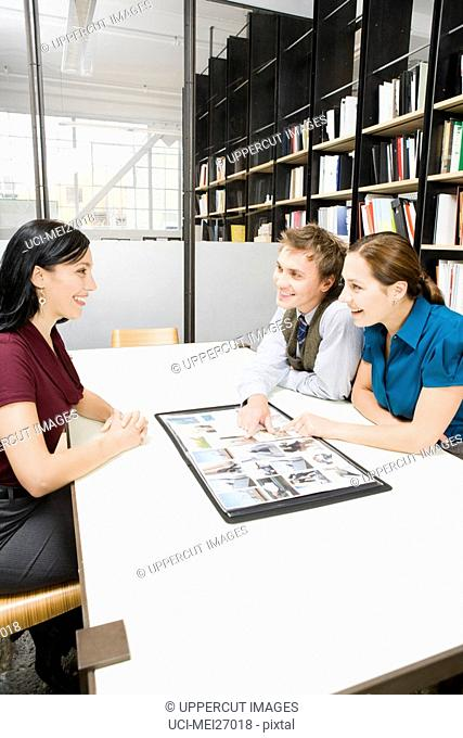 Young businesspeople looking at portfolio