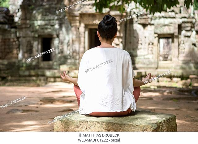 Cambodia, Angkor, Siem Reap, back view of young woman practicing yoga in front of Ta Som temple