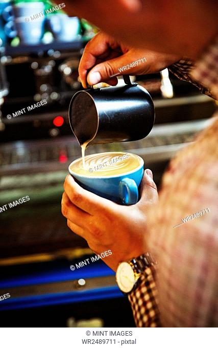 Specialist coffee shop. A barista pouring hot milk in to the froth on a cup of coffee to make a pattern