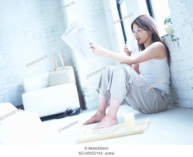 Woman reading newspaper on floor