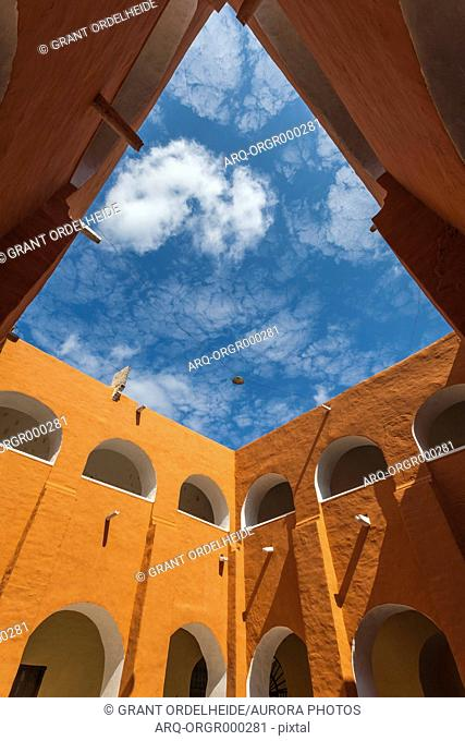 Orange colored courtyard under blue sky and clouds, Izamal, Yucatan, Mexico