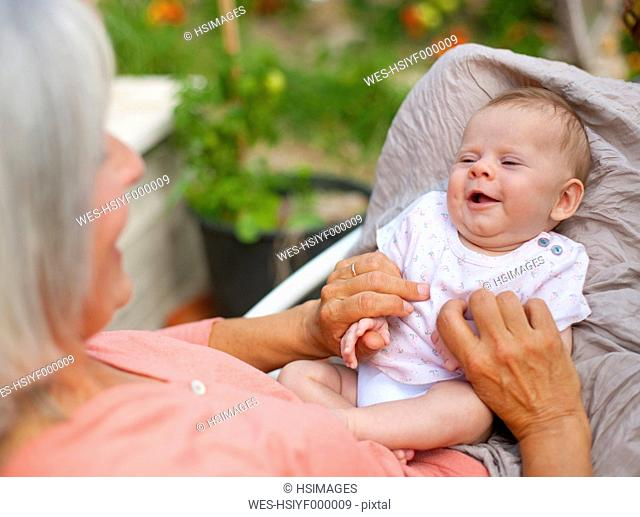 Germany, Bavaria, Woman with grandchild sitting in lawn chair, smiling