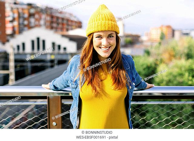 Portrait of smiling young woman wearing yellow cap and dress