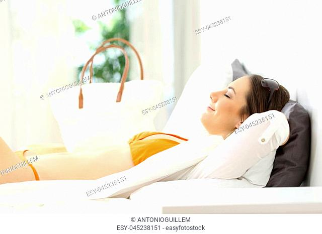 Happy woman relaxing lying on the bed of an hotel room on summer vacations