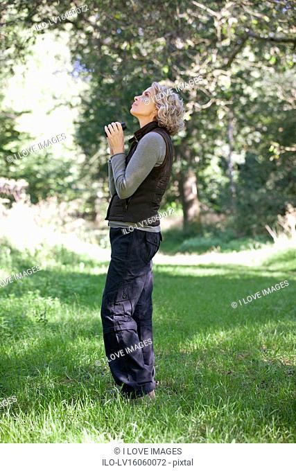 A mature woman outdoors holding a pair of binoculars looking upwards