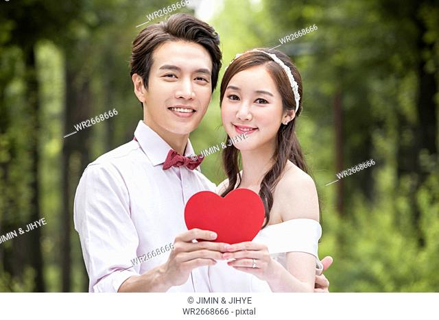 Portrait of young romantic couple with heart outdoors