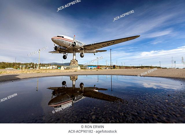 The Douglas DC-3 weathervane its nose pointed into the wind and reflected in a water puddle outside the Yukon Transportaiton Museum in Whitehorse, Yukon, Canada
