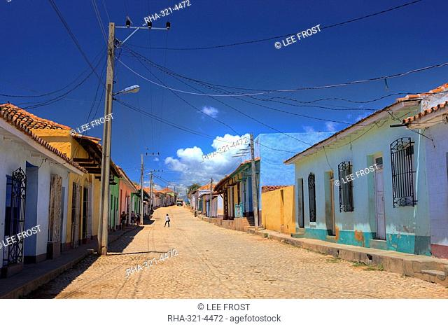 View along cobbled street lined with bright-painted houses, Trinidad, Cuba, West Indies, Central America
