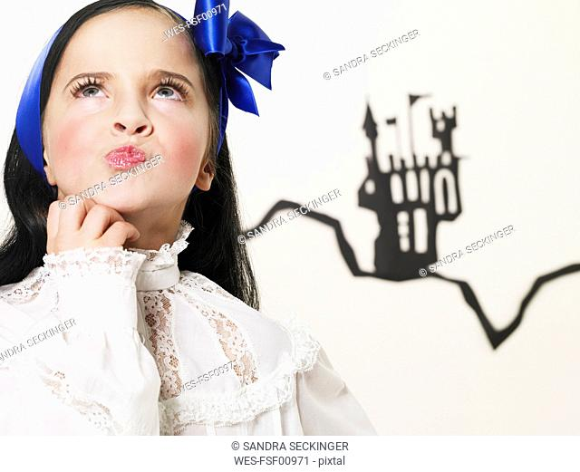 Portrait of little girl dressed up as Snow White looking up