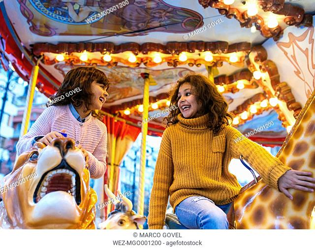 Two laughing little girls having fun on a carousel