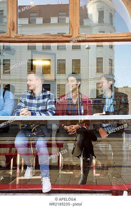 Male friends sitting in cafe seen through glass window