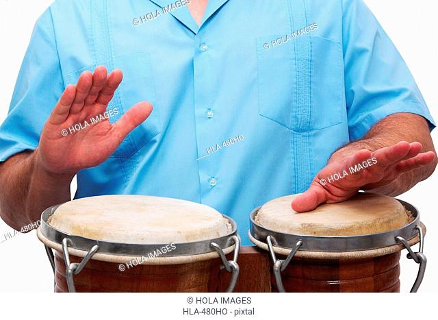 Mid section view of a man playing bongo drums