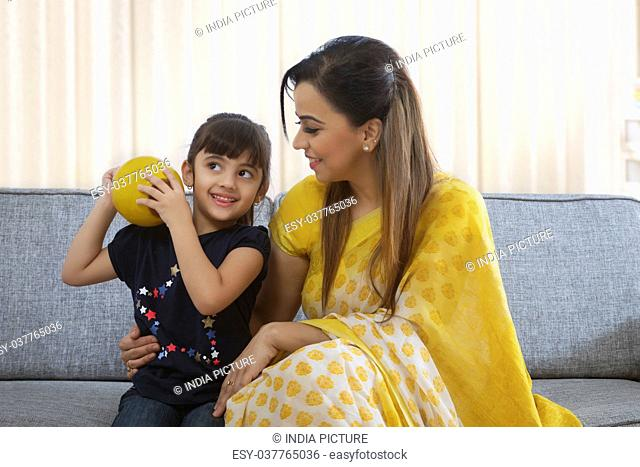 Girl shaking clay piggybank and mother looking at her