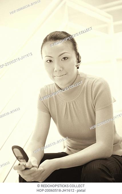Portrait of a businesswoman sitting on a staircase and holding a mobile phone