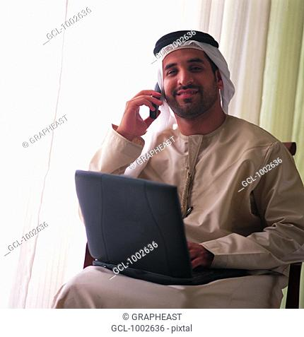 Businessman with cell phone and laptop