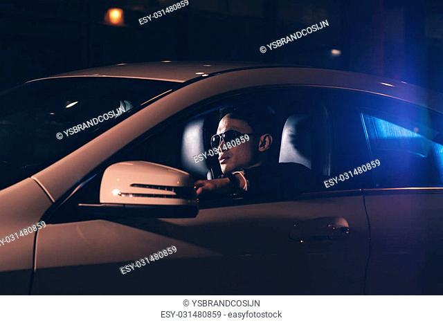 Side view of asian man with sunglasses in car at night