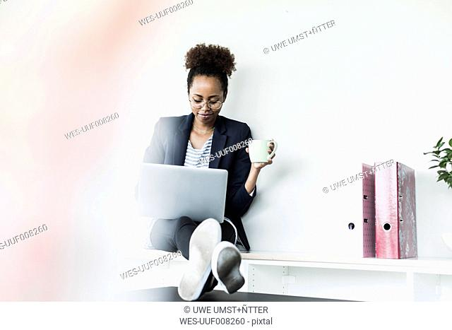 Smiling businesswoman with cup of coffee using at laptop
