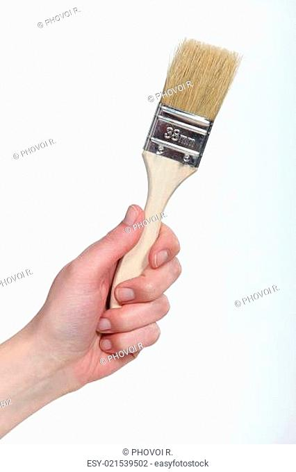A picture of a hand holding a painting brush