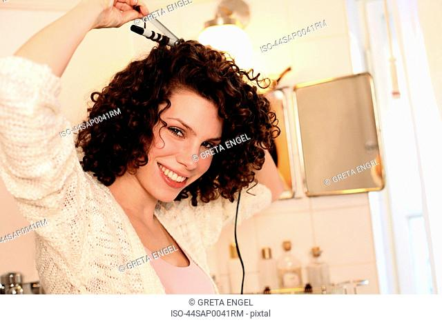 Smiling woman curling her hair