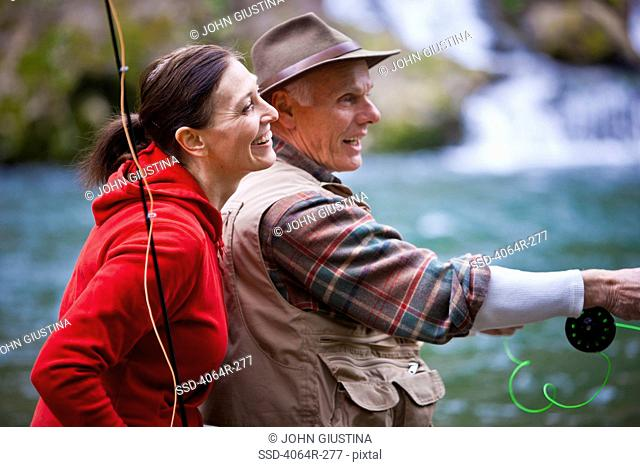 USA, Washington, Vancouver, Smiling couple fishing in river