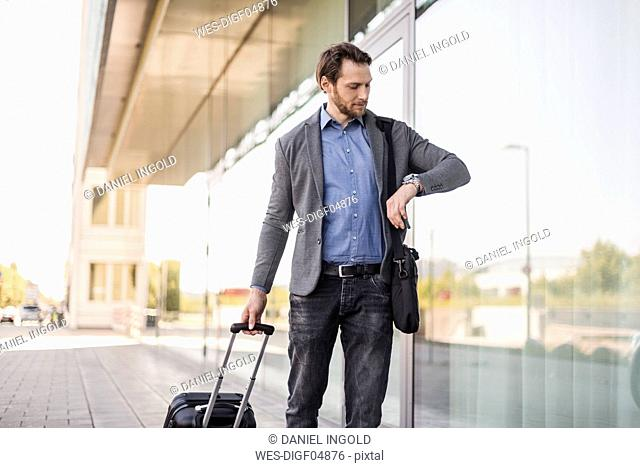 Businessman with rolling suitcase and laptop bag checking the time