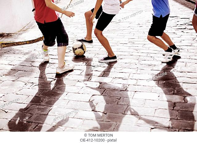 Children playing with soccer ball in alley