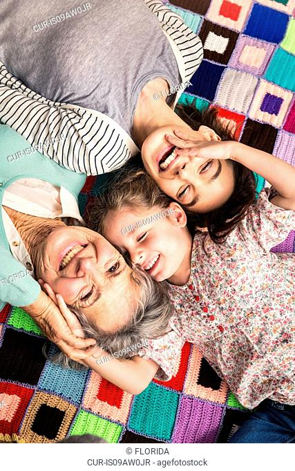 Overhead portrait of girl with mother and grandmother lying on patchwork blanket