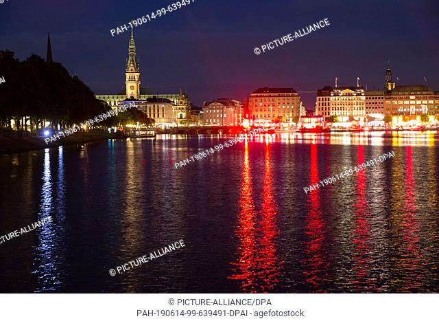 13 June 2019, Hamburg: The Jungerfernstieg and the Binnenalster are illuminated with red light in the evening. The light artist Michael Batz dips the...
