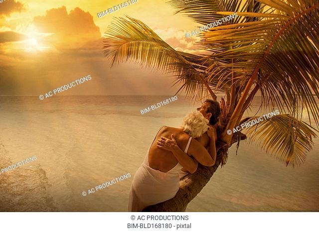 Older Caucasian couple hugging on palm tree at beach