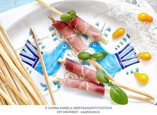 Breadsticks wrapped in prosciutto, decorated with fresh basil and yellow pear tomatoes
