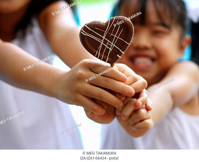 Close-up of two girls holding a heart shaped lollipop