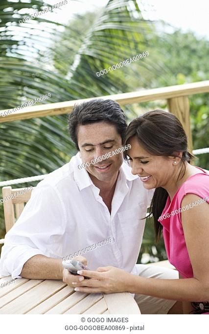 Couple using cell phone at picnic table