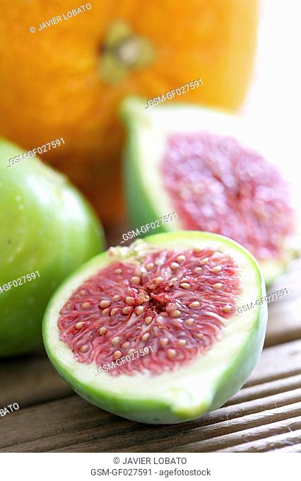 Close up of an opened fig with an orange in the background