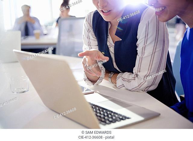 Businesswomen talking, working at laptop in office meeting