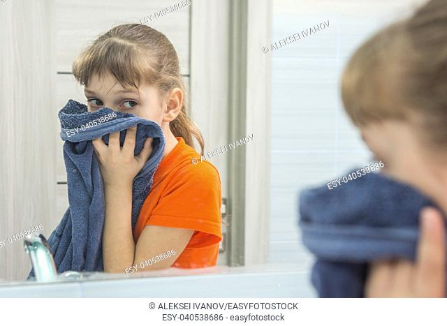 The child wipes his face with a clean towel in the bathtub