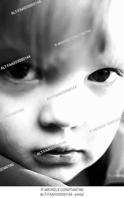 Little boy frowning at camera, portrait, close-up