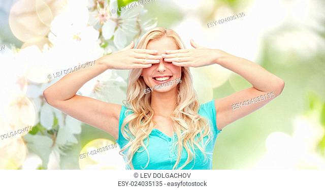 emotions, expressions and people concept - smiling young woman or teenage girl covering her eyes with palms over natural spring cherry blossom background