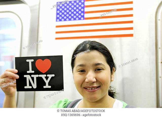 Hispanic, Asian, woman holding 'I Love New York' postcard, Subway train metro station, New York City