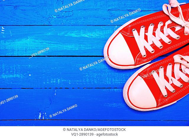 pair of bright red textile sneakers on a blue wooden background of boards, top view, empty space