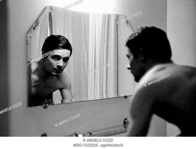 Jacques Charrier looking at himself in a mirror. French actor Jacques Charrier looking at himself in the mirror of a bathroom. Paris, 1959