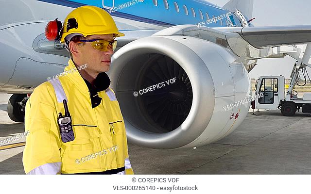 Person looking at his charts and communicating, while standing in front of a plane