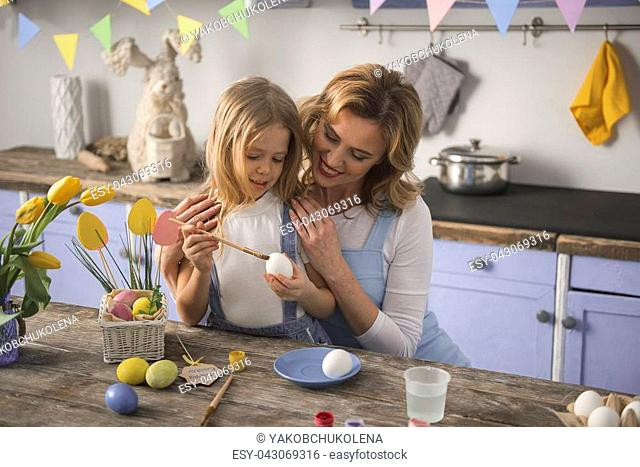 Team work. Satisfied mother is hugging daughter in the kitchen. She is watching as her child making colored eggs. Copy space in right side