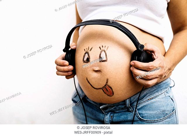 Pregnant woman holding headphones at her painted belly