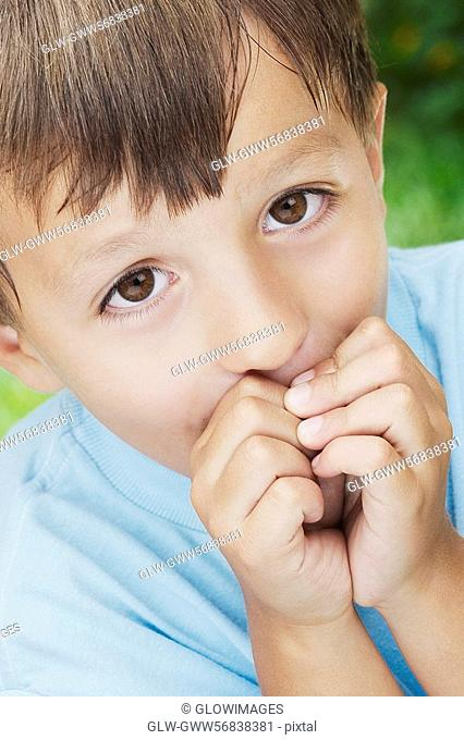 Close-up of a boy with his hands covering his mouth
