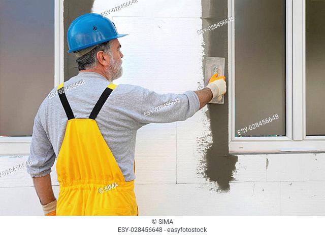 Worker spreading mortar over styrofoam wall insulation with trowel