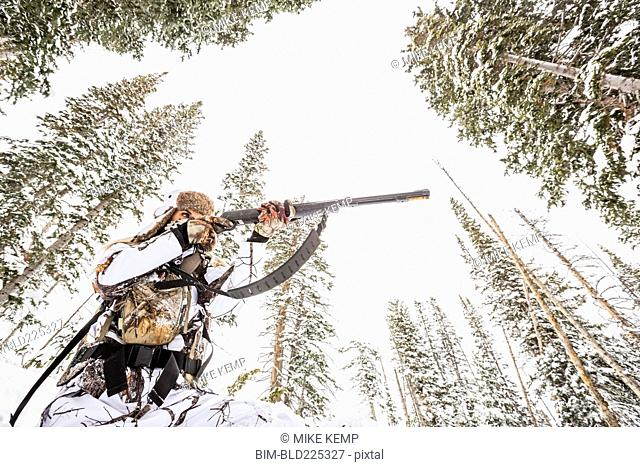 Caucasian woman hunting in forest aiming rifle