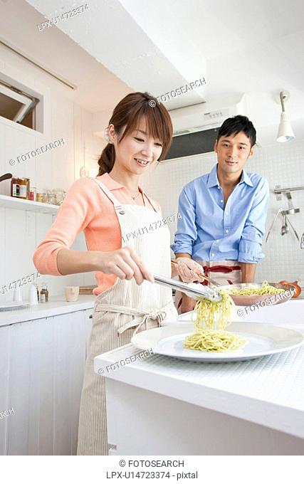 Young woman serving pasta