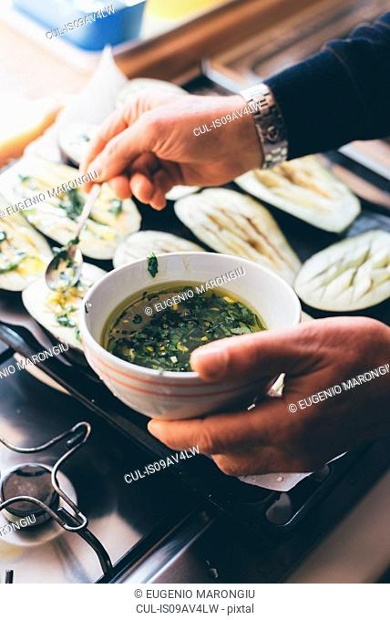 Mans hands drizzling herb oil on aubergine halves in kitchen
