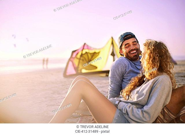 Laughing couple relaxing on sunny beach